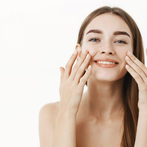 Waist-up shot of charming relaxed and gentle young woman making cosmetological procedure applying facial cream on face with fingers and smiling broadly feeling perfect, taking care of skin. Beauty and skincare concept